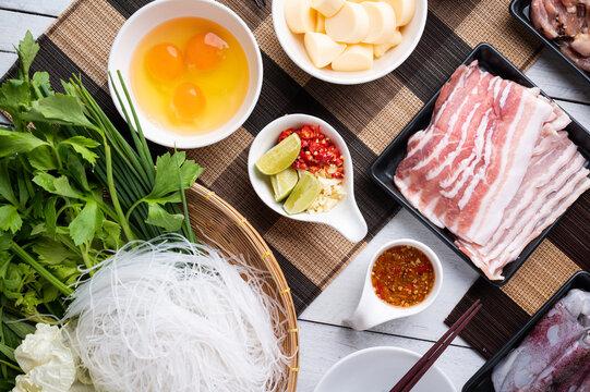 Sukiyaki . Preparation of raw materials,beef,egg ,tofu,vegetable and mung bean noodle  for sukiyaki using hot pots.
