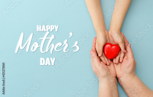 Concept Happy Mother's Day or International Day of Families.Happy women's day.Heart in the hands of daughter and mother on a blue background.I love you.Banner for store.Greeting card. Top view