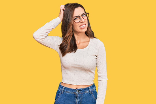Young brunette woman wearing casual clothes and glasses confuse and wonder about question. uncertain with doubt, thinking with hand on head. pensive concept.