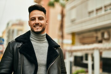 Obraz Young arab man smiling happy standing at the city. - fototapety do salonu