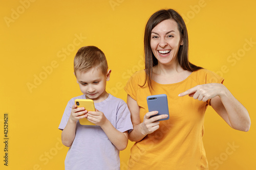 Happy young woman have fun with cute child baby boy 5-6-7 years old in violet t-shirt hold use mobile phone. Mommy little kid son together isolated on yellow background studio Mother's Day love family