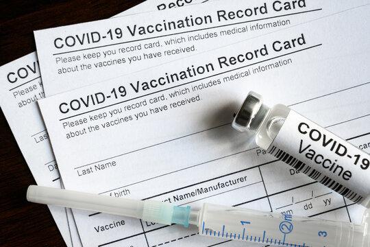 COVID-19 Vaccination Record Card on desk, coronavirus immunization certificate for travel