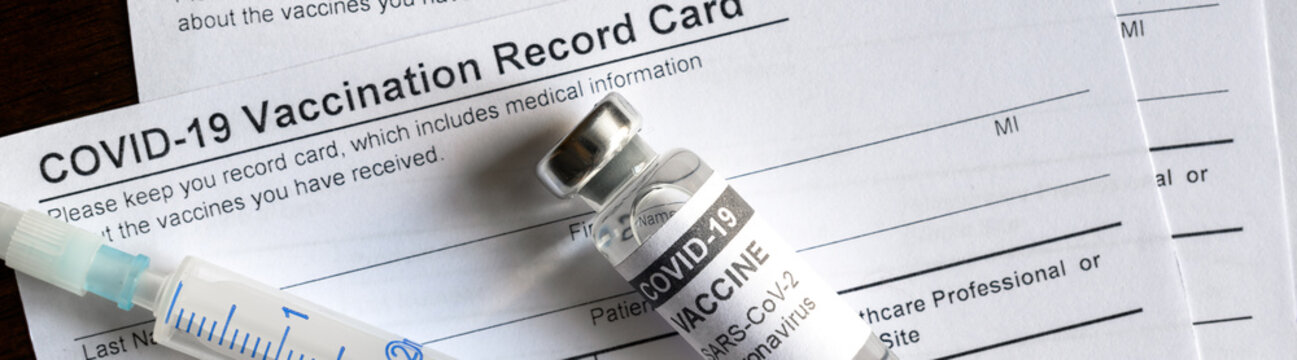 COVID-19 vaccine bottle and syringe are on coronavirus Vaccination Record Card