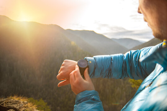 Hiker in the mountains checking stop watch on the sports watch. People in the mountains. Sports.