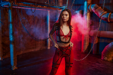 Sexy woman in red bdsm suit chained up
