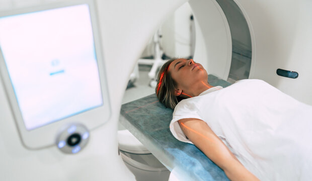 Young woman patient is ready to do magnetic resonance imaging in the modern hospital laboratory