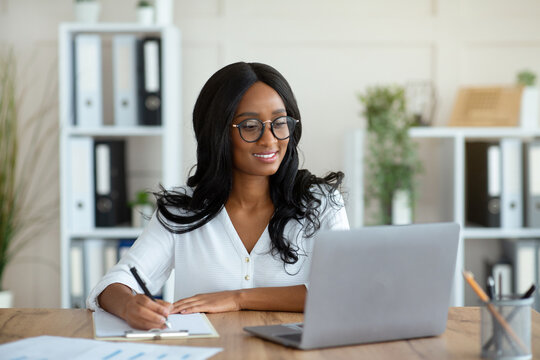Cheerful black business lady working on laptop, taking notes during online work meeting or webinar at office