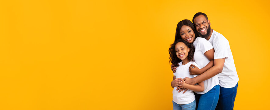 African American man hugging his wife and smiling daughter