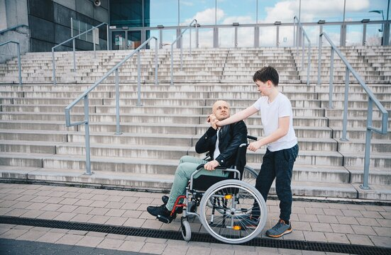 Disabled handsome man in wheelchair giving high-five to son in walk.