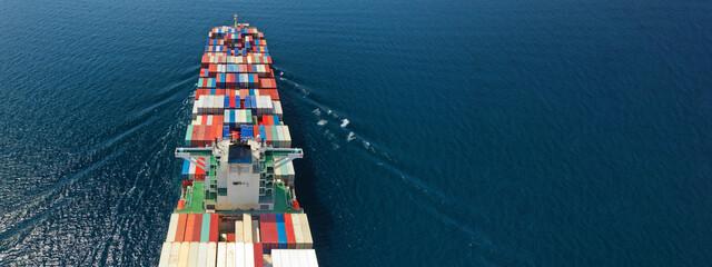Fototapeta Aerial drone ultra wide photo of huge container ship cruising deep blue open ocean sea near logistics container terminal port