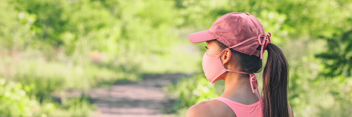 Fototapeta Mask covid-19 outside lifestyle woman walking at outdoor park wearing pink face cover for coronavirus prevention.