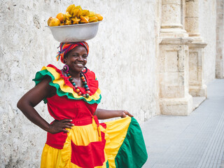 Traditional fresh fruit street vendor aka Palenquera in the Old Town of Cartagena in Cartagena de...