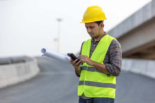 construction worker holds blueprint and typing a message on smart phone at construction site