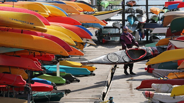 A woman returns a kayak after paddling on a sunny day on the waterfront in Toronto