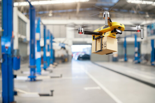 Flying delivery drone transferring parcel box from distribution warehouse to automotive garage customer service repair center background. Modern innovative technology and gadget concept.