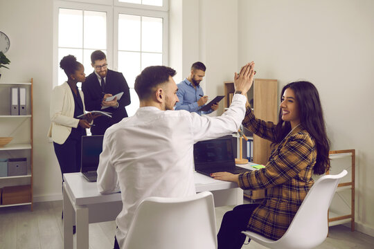 Well done. Happy enthusiastic people high-five each other sitting at table in coworking office. Productive business meeting, work together, making deal, success, commitment, positive attitude concept