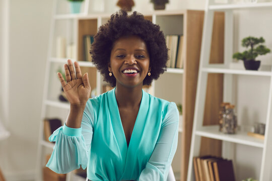 Friendly african american business woman waving her hand in greeting over a video call. Female worker sits in front of a webcam and communicates during an online conference. Online meetings concept.