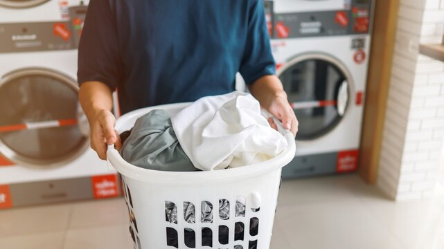 Man doing launder holding basket with dirty laundry of the washing machine in the public store. laundry clothes concept