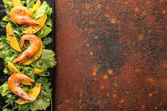 Plate of fresh mango salad with shrimps on grunge background