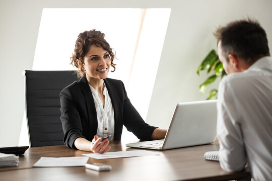 Portrait of a smiling businesswoman talking to a client.
