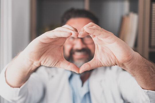 Close up portrait of smiling young caucasian male nurse or GP in white medical uniform show heart love hand gesture. Happy man doctor show support and care to patients or client in hospital..