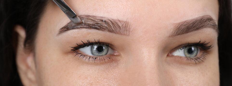 Beautician applying tint during eyebrows correction procedure on light grey background, closeup