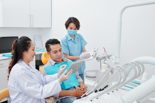 Smiling dentist showing tablet computer with teeth x-ray to patient and explaining what to expect from treatment when assistant taking notes in document