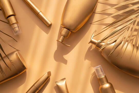 Golden clean bottles of cosmetics, palm gold leaf on beige background. Cosmetic mock up bottles, tubes. Branding products, spa, beauty summer background Flat lay top view copy space. Place you design