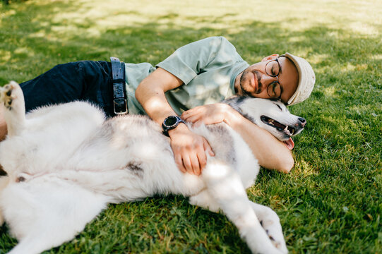 A lovely man lying with a dog on the grass