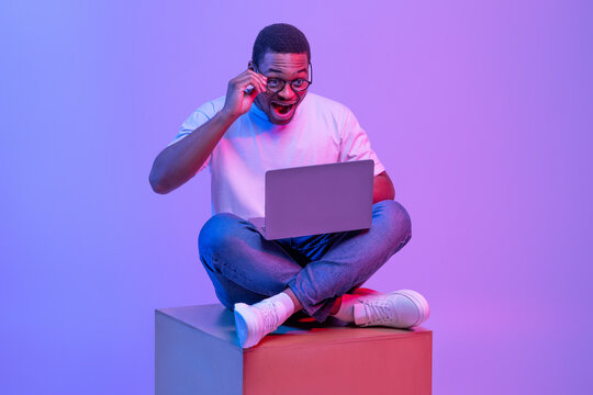 Excited Black Male Sitting On Big Cube With Laptop, Looking At Screen
