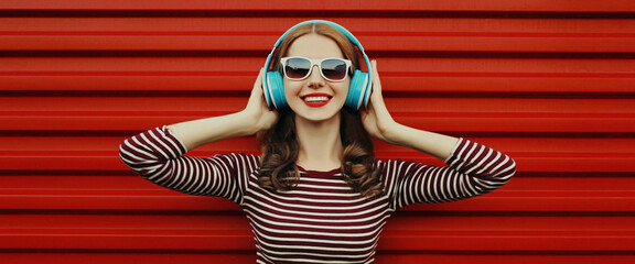 Portrait of happy young woman with wireless headphones listening to music on a red background