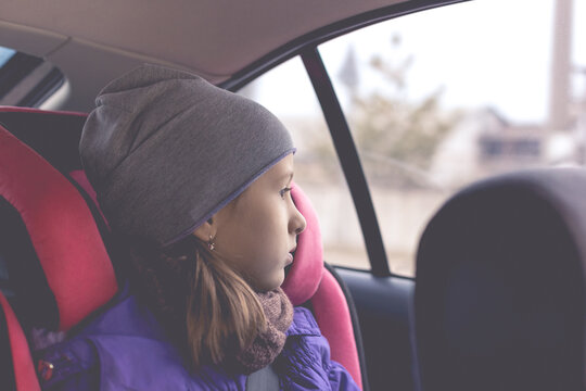 Little girl sit in the car seat and looks out the window