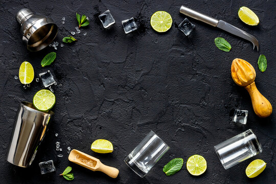 Frame of bar equipment and cocktail ingredietns - shaker, lime and ice. Overhead view
