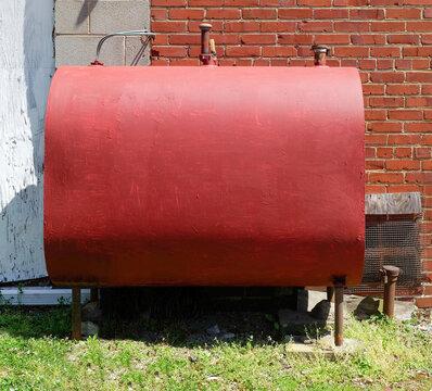 Freshly red painted home heating oil tank.