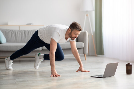 Positive bearded man exercising at home, using laptop