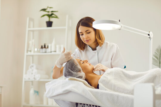 Woman getting facial beauty injection with syringe from woman cosmetologist
