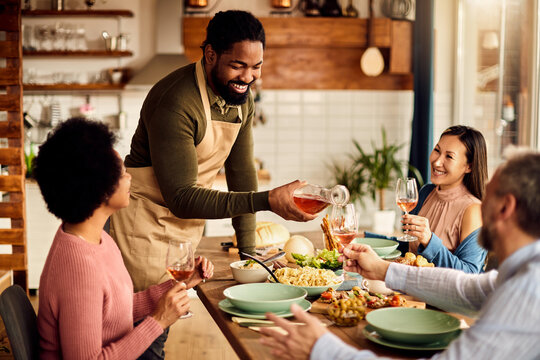 Happy African American man serving wine to his friends while having lunch at dining table.