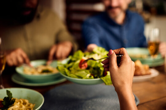 Close-up of black woman eating salad while having lunch with friends at dining table.