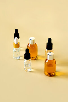 glass bottles for cosmetics, natural medicine, essential oils or other liquids on a beige background