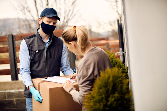 Delivery man with face mask holding cardboard box while customer is signing document for received home delivery.