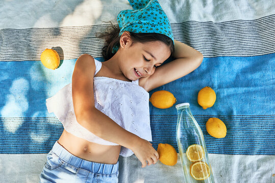 View from above of a cute little girl lying on the picnic blanket with lots of lemons in the park. Kid having cozy summer picnic with family. Child resting outdoor.