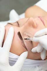 Fototapeta Kosmetyczka robi makijaż permanentny brwi, tatuaż na twarzy kobiety. Zbliżenie na proces pigmentacji brwi.  obraz