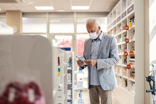 A patient in a pharmacy. An older man with gray hair in an elegant suit holds medication in his hand and reads therapies. He is in a pharmacy lit by daylight. Protective mask against corona virus