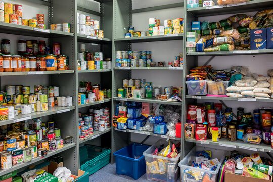 ROTHERHAM, ENGLAND, UK – FEBRUARY 14, 2019: Storage shelves in a Trussell Trust local church food bank warehouse showing a variety of tins and store cupboard essentials ready for food parcels