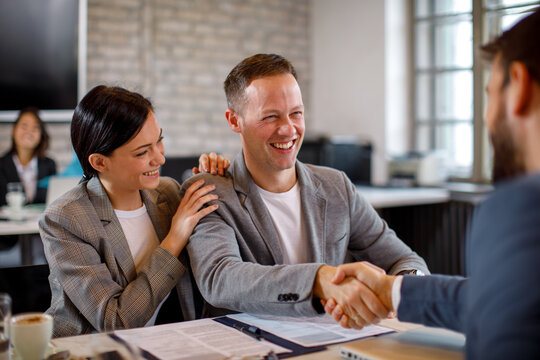 Happy young couple make a deal with their personal financial advisor in bank