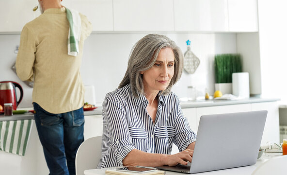 Mature mid aged 50s woman wife remote working or distance learning online from home office using laptop computer while her senior husband cooking breakfast in kitchen, helping with household work.