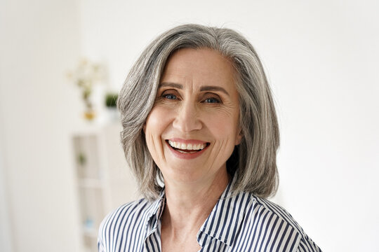 Cheerful satisfied 50s mature woman laughing looking at camera at home. Happy sophisticated classy mid age older gray-haired lady with white teeth dental smile posing for close up headshot portrait.