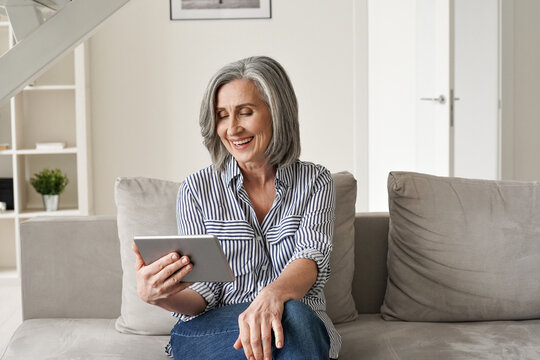 Happy old mature mid age senior woman using digital tablet looking at computer virtual calling having online meeting, watching tv, reading e book spending time with tech device sit on couch at home.