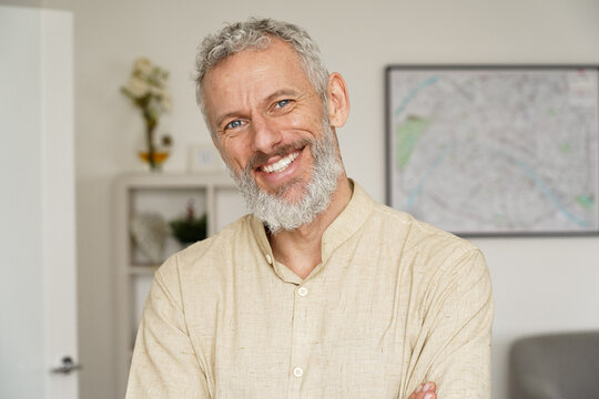 Smiling relaxed mature older bearded hipster man looking at camera. Happy handsome confident middle aged 50s male professional, standing at home office posing indoors for close up headshot portrait.