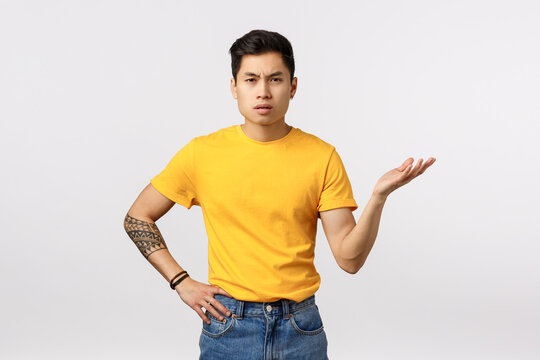 So what. Skeptical and pissed, frustrated young asian guy dont understand whats big deal, why so fuss, raising arm in dismay, standing puzzled and bothered as arguing with friend, white background